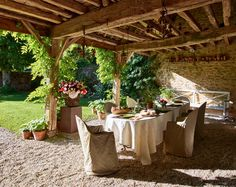 Outdoor Space /  At fashion designer Peter Copping's Normandy, France, château, a table is set for a luncheon in the former stables. /      Photographer: Richard Powers     Homeowner: Peter Copping and Rambert Rigaud     Article: French Connection, September 2015     Location: Normandy, France