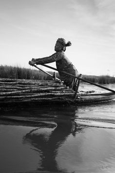 John Vink. CAMBODIA, Prey Nob (Preah Sihanouk). 6/08/2015: A woman navigates her boat carrying wooden poles through the maze of canals criss-crossing the polders containing 10500 hectares of rice fields protected from sea water by a 16 km-long dam. Motorised traffic is prohibited on the dykes