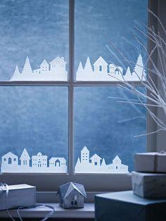 Бумажные домики на окнах.