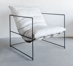 Minimalist lounge chair looks like its floating in its frame. By Croft House.