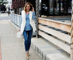 Eva Amurri Martino of lifestyle blog Happily Eva After wearing dark denim maternity jeans, a light chambray maternity top, white vest, and light brown western style booties walking down the street in connecticut