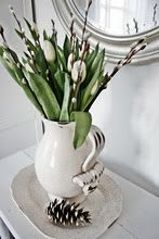 White Tulips and Pussy willows in a white stoneware pitcher.