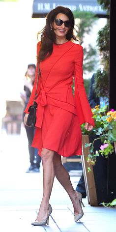 Look of the Day - Amal Clooney in a bold. long-sleeve Proenza Schouler  dress knotted at the waist, styling it with a mini cross-body Proenza purse and nude pumps.