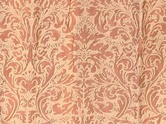 FORTUNY CURTAINS, 20TH CENTURY  the salmon pink ground printed with silver grey arabesques, comprising three pairs of matching curtains with matching fabric covered pelmets; each with a pair of pink cord tasselled tie backs, each curtain 116in. (296cm) drop x 40in. (102cm) gathered width; pelmets each 75 x 33in. (191 x 83cm); and a matching footstool with tasselled trim I Christie's Sale 4978
