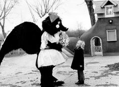"""Michelle Zuerlein, 7, is the first in line to meet Peony the skunk, the newly unveiled mascot of the park at 78th and Cass Streets. According to The World-Herald story on March 18, 1974, park officials were looking for a symbol """"a la Mickey Mouse for the Disneys."""" The trademarked skunk costume was purchased for $1,100, and it was air conditioned using a portable unit that was developed for astronauts. Peony the skunk was to roam the park that summer spreading cheer. THE WORLD-HERALD"""