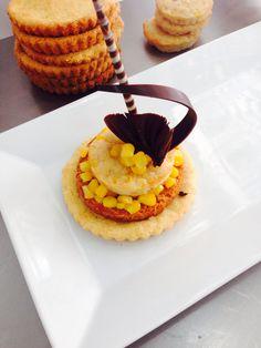 Mini tarta de elote compuesta de sable de almendra, biscuit de especias y de almendra decorado con elotito confitado y chocolate