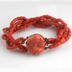 Antique bracelet of 4 strands of dark salmon red Italian coral beads attached to a gold filled box clasp with carved coral flower. The clasp measures 3/4 inches in diameter and 3/8 inches deep. Bracelet has a total length of 8 inches.