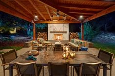 Bistro lights and stone pavers lead the way to this stunning outdoor space from Nar Fine Carpentry. Here, wood beams and open siding ensure that the structure complements the landscape, while a dining table and sitting area make room for guests.