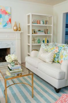 Aqua accents in shades of sea glass: striped rug, art, pillows, and accessories.