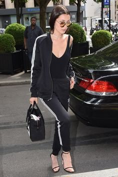 Bella Hadid wearing Adidas Superstar Cuffed Track Pants, Stuart Weitzman Nudist Pumps, Quay Circus Life Sunglasses, Celine Luggage Tote, Danielle Guizio Two Row Pave Choker, Adidas Supergirl Track Jacket and Are You I Am Naia Bodysuit