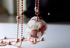 A hand-blown glass bead with rose petals and white limonium. The work of art hangs on a long high-quality ball chain. All items are gold-coloured alloy rosé.  Please remove while showering, bathing, etc., the flower can of bear damage if water penetrates the glass bead. Because it is a natural product, each chain looks slightly different.  Size/weight Chain 76cm Glass ball (flower, flower) approx. 2,2 cm in diameter  The materials used Chain and clasp rose gold-tone brass Glass ball Pres...