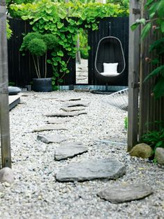 Wooden garden fence hanging chair stone path pebble