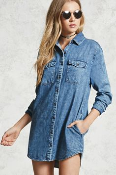 A short length denim shirt dress featuring a partial button front, collar, two front button flap pockets, two front slanted pockets, and long button cuff sleeves.