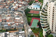 Such an interesting contrast of the extravagence that wealth brings vs poverty: I think an interesting point to bring up is the fact that whats not shown here, is all the people who are living in between those smaller homes.. people who have nothing and live on the streets... now look at all the space that this grand hotel and tennis court and pool are taking up, and imagine how many more homes could have been put there instead...