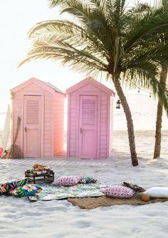 Cabane en bois peinte en rose avec des palmiers