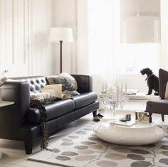 Elegant and light living room with black leather sofa, white walls and neutral rug / Salón elegante y claro con sofá de cuero negro, paredes blancas y alfombra en tonos neutros