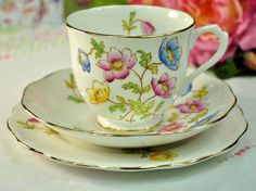 Royal Albert Anemone pattern vintage bone china teacup, saucer and tea plate trio. c.1940s Gorgeous Royal Albert china with hand painted pink, blue and yellow anemone flowers and green foliage. Gold gilding to the teacup base and all rims. Teacup 8cm wide at the rim x 7cm tall approx. There is a little pink anemone flower inside the rim. 14cm wide saucer and 16cm wide tea or side plate. Made by Thomas C. Wild, St.Mary's Works, Longton, Staffordshire, England. In excellent condition.