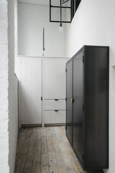 """The Plain English team designed a wall-hung, blackened-steel cupboard """"in the manner of a school locker""""—and floated it off the ground: """"This area is narrow, so to keep the cabinet from sitting heavily in the space, we raised it,"""" says Milne. Throughout she stuck to a materials palette of painted wood, blackened and stainless steel, marble, and brass."""