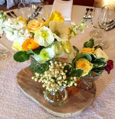 Local array of vases on wood slab disk. Peonies, ranunculus, brazillia, roses, daffodils, anemones. Yellow, white, cream Spring Wedding centerpiece at Mill Valley Outdoor Art club. Http://ggboutique.com