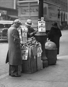 An unemployed man selling apples in a wooden crate for five cents during the Great Depression.