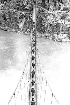 Riding horses on a suspension bridge over the Snake River, Oregon. Coming from the Idaho side, 1950. --  Gerald W. Williams Collection, Oregon State University Libraries