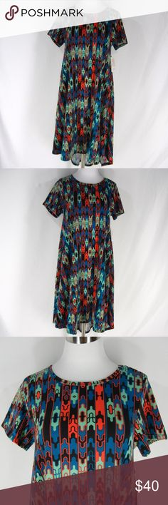 """New LULAROE Carly Dress S Stretch Multi Geo Puzzle LULAROE Carly Dress in a colorful geometric puzzle pieces type print.  Scoop neckline, short sleeves, one chest pocket, a line tunic shape, high low hem, lots of stretch.  96% polyester, 4% spandex, machine wash.  Made in the USA.  New with tags.  Size S, please check measurements to determine fit.  36"""" chest, 48"""" waist, 62"""" hips, 38-43"""" long. LuLaRoe Dresses"""
