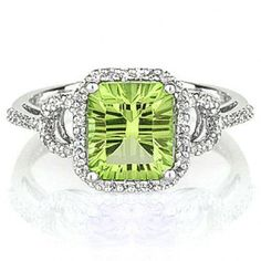 14k white gold peridot and diamond ring. Featuring a unique cushion shaped fantasy cut peridot weighing 2.21cttw accented by a halo of .18cttw of round diamonds. Makes a great August birthstone ring.