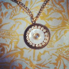Detailed mother of pearl button surrounded by antique crystals.