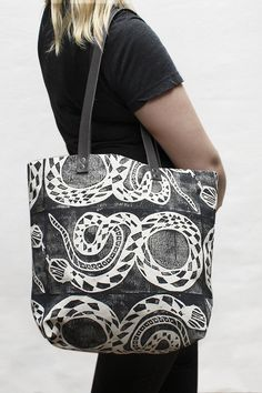 "A sturdy natural canvas tote bag with a hand printed block design in black ink. Dimensions: Measures 12.5"" x 16"" x 4.75"". Details: Black leather straps with a 12"" drop. Includes interior pocket for ea"