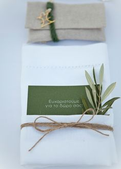 Linen hemstitch napkins tied with twine, a thank you note and olive tree branch! The handmade wedding favor with a lucky charm bracelet, complements the country chic table set up!!