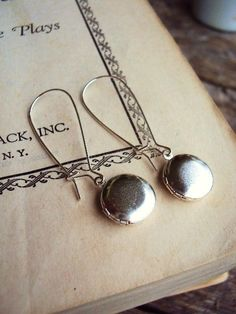 These are long earrings, with miniature vintage lockets. The lockets are a matte silver plate. These dangle from long kidney wires. They are light weight, and great for everyday wear. The earrings drop 2 in. long, and the lockets are 13mm around. The pair is in wonderful unused condition. Thank you for looking