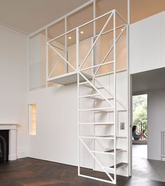 A metal-framed staircase leads to mezzanine floor inside this newly renovated flat in west London, but it also doubles up as climbing frame for the owners to practice circus tricks (+ slideshow).
