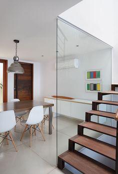 Apartamento, decoração de apartamento, com tons neutros. Mesa de jantar retangular de madeira com cadeiras brancas, quadros e pendente.