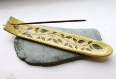 I made this ceramic incense holder from white earthenware clay before carving in a natural design of leaves growing from a spiral. Yellow and green slips were used to bring soft natural colour to the piece before firing. This piece is now sold but custom requests are welcome. https://www.etsy.com/uk/transaction/110352133?