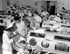 Nurses and doctors assist patients with polio in an iron ward during a 1950s polio epidemic.