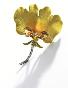 Gold, Enamel and Diamond Orchid Brooch, Tiffany & Co., Designed by Paulding Farnham Designed as the variety of orchid 'oncidium varicosum rogersii,' the petals decorated in vibrant yellow and faint orange enamel, accented by the lip with yellow, ochre and cream-colored enamel bordered by rose-cut diamonds, the descending curled sepals of chartreuse and orange-hued enamel supported by a column of rose-cut diamonds, circa 1890.