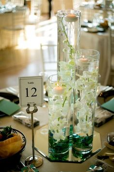 An array of different sized cylinders with floating candles and flowers inside!  Ethan Yang Photography