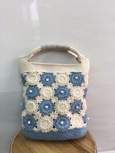 『初夏ハンドメイド2016』天然染めの優しい色合いでOHANAモチーフのミニバッグを作りました。素材はオーガニックコットン100%の編み糸を使用。空色のブルーは本藍で染めています。裏地はリネン100%の生地で小さいながらしっかり目の作りになっています。お散歩からちょっとしたお出掛けまで、これからの季節のコーディネートに活躍しそうです。 素材    表   オーガニックコットン糸  100%       裏   リネン生地  100% サイズ   タテ  約28cm( 持ち手部分含まず )       ヨコ  約25cm        ✽ お洗濯について  ウッドビーズを使用しているので基本的には水洗いできません。  持ち手部分の汚れなどは部分的に手洗いしていただく様お願いいたします。 ✽ 天然染料で染めておりますので、多少色落ち、色移りいたします。  淡色の衣類などに合わせられる場合は摩擦などにより色が移ってしまう場合  がありますのでご注意ください。