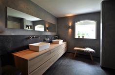 Sober en stoer betonstuc van Herijgers Badkamers - www.herijgers.nl Maatwerk houten badmeubel en donkere tegels