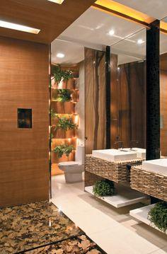 Banheiro-  O piso de porcelanado é produzido com 20% de materiais recicláveis e as tintas, com garrafas PET. As bancadas apresentam cubos sobrepostos de mármore marrom-imperial, reproduzindo um mosaico de pedra. Um arranjo inusitado é feito com os cachepôs de plantas que ficam acomodados no painel ondulado de chapas de cob