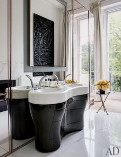 A work by Aaron Curry is reflected in the mirror of this master bathroom | archdigest.com