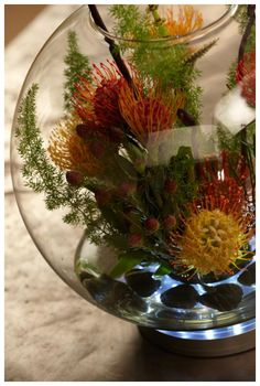 "Flower Arrangement Tips to Think Outside the Vase : Think beyond the petal to create interesting and unusual arrangements such as this one using the Pin Cushion Protea. I think this flower has a sci-fi vibe with its futuristic tentacle-like arms. Schwanke created a fish bowl vignette for an ""under the sea"" look by securing the Pin Cushion flowers with metal pin holders known as flower frogs."