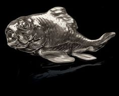 A Silver Salt Shaker in the Form of a Fish by Fabergé, workmaster Hjalmar Armfeldt, St. Petersburg, 1908-1917. Realistically modeled, the mouth open and pierced, the base flat with ivory sliding panel.