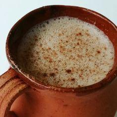 Chocolate de molcajete en olla de barro espumado con molinillo y un toque de canela