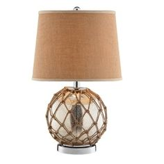 Marina Table Lamp Japanese Fishermen use glass floats like the one seen on the Marina table lamp to keep their nets afloat. This lamp was modeled after those floats and its mottled glass base has been wrapped with hand-knotted rattan rope. This distinctive table lamp offers an antique mercury glass and rattan construction and a metal base, with a fabric hardback shade with tan trim. #Coastal #Beach #HomeDecor
