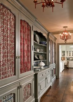"""""""nearly every cabinet front in the butler's pantry features a different shirred fabric insert, and even the hardware is mismatched"""""""