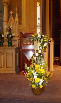 Paschal Candle, Easter 2014 Holy Cross Church, Santa Cruz CA. The garland is silk flowers, the vase contains real flowers. The paschal candle should be venerated and celebrated in a special way during the Easter season.