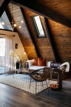 A 1970s A-Frame Cabin in Big Bear Is Brought Back to Life - Photo 4 of 12 - Picks from West Elm furnish much of the living space, including the chandelier, coffee table, and rug. A leather Article sofa sits next to a pendant light from Anthropologie. #BigBuildings