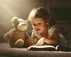 Child little girl reading a magic book in dark home. Child little girl reading a ,