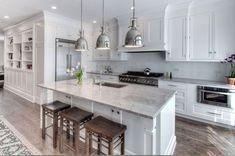 Very familiar! Shaker style white cabinets, custom hood, polished nickel pendants and kashmir-like granite. Next up - slide in gas range and counter depth fridge.